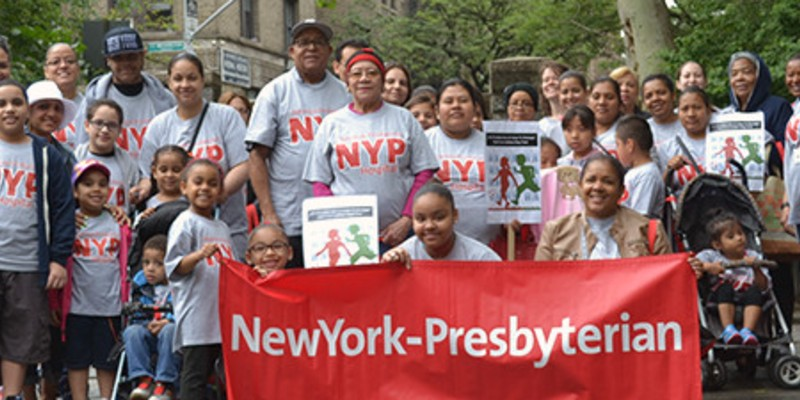 Community members posing with a New York - Presbyterian banner