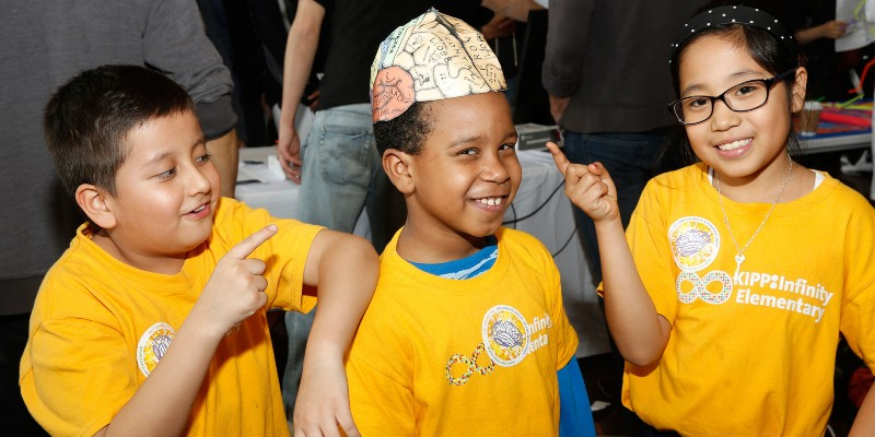 "Three children in yellow ""KIPP Infinity Elementary"" t-shirts smiling and pointing to the brain diagram hat the middle child is wearing."
