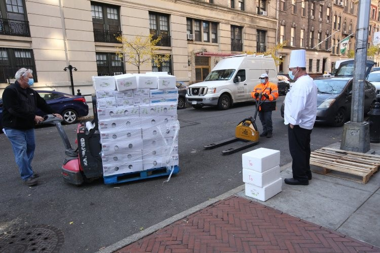 A man wheels a flat of boxes that contain frozen turkeys.