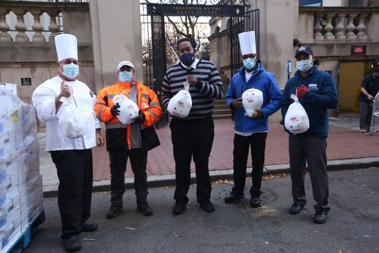 Five people in masks display the frozen turkeys in bags to the camera.