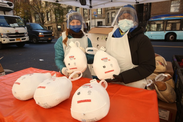 Two volunteers in masks and face shields hold turkeys up for the camera.