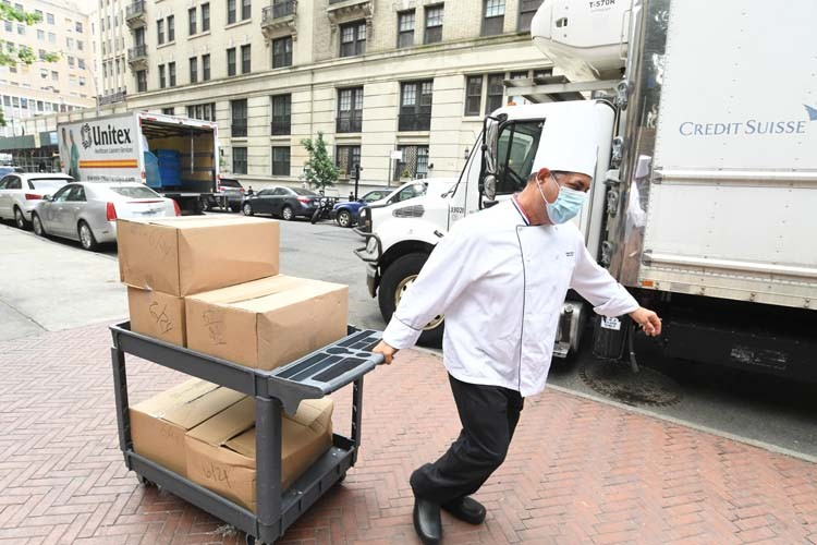 Columbia dining employees transport using hand cart.