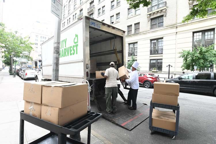 Columbia dining employees load numerous trucks using hand cart.