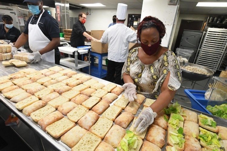 Columbia dining employees create meals in kitchen.