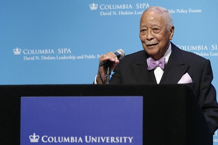 David Dinkins speaking in front of blue screen.