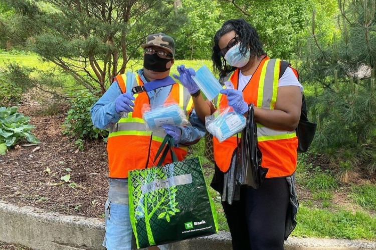 Two volunteers in orange vests with masks for distribution