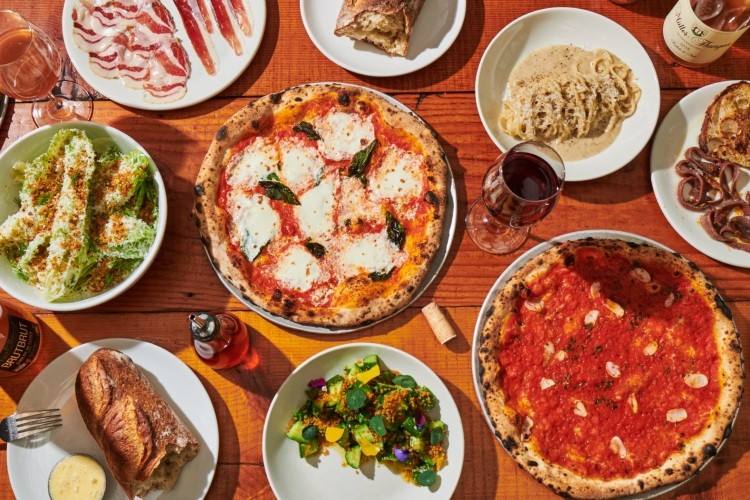 Photo of table with multiple dishes on it, featuring two pizzas.