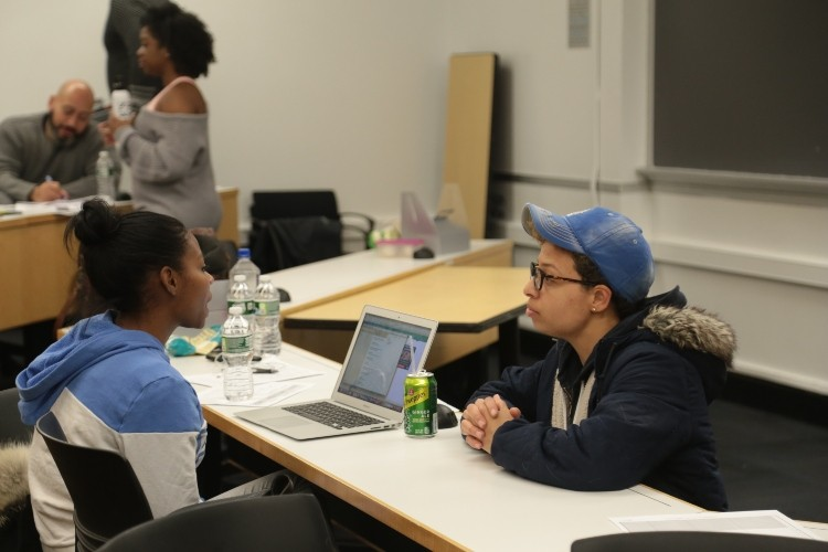 Two students in a class room discussing something while looking at a laptop