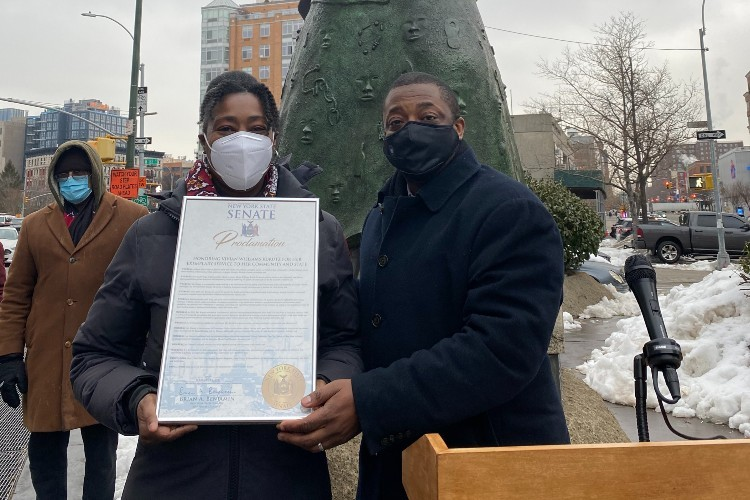 A woman and a man standing in front of a statue, both wearing masks. The woman is holding a New York State Senate proclamation.