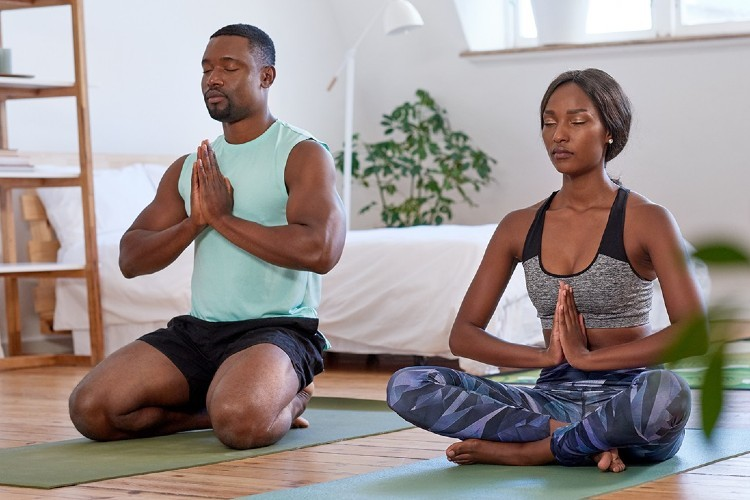 A man and a woman sitting on yoga mats meditating together.