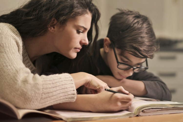A girl and a boy studying from a textbook together.