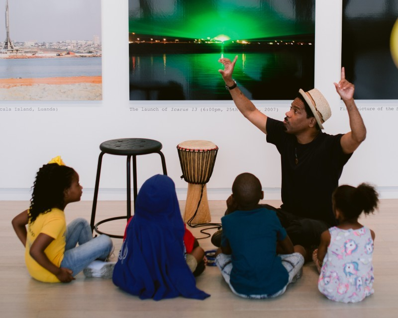 A man speaks to a group of children about art that's visible behind him.